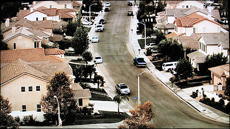 Next, We Look Down On A Suburban Street, Where The Houses Have Red Tile  Roofs.
